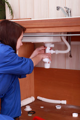 Female plumber repairing sink