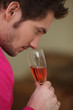 Young man smelling a glass of wine