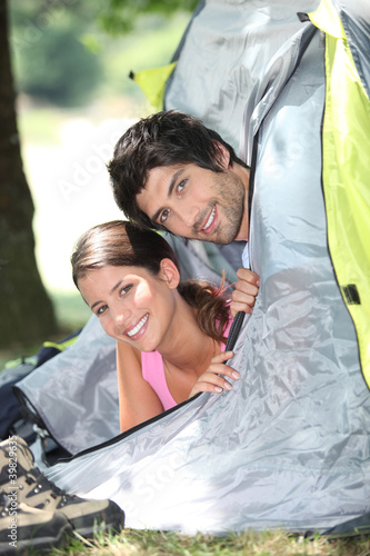 Young couple sticking their heads out of a tent door