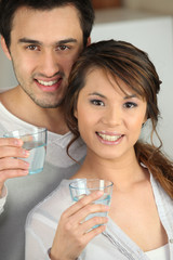 Enthusiastic man and woman with glasses of water