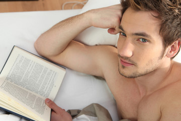 Man in bed reading book