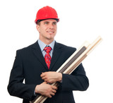 Handsome smiling engineer with hard hat and blueprints