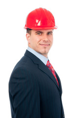 Portrait of handsome smiling engineer with red hardhat