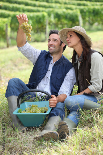 Farmer and wife sat with basket of grapes