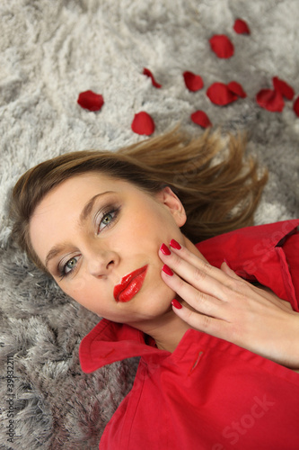 Woman lying surrounded by rose petals