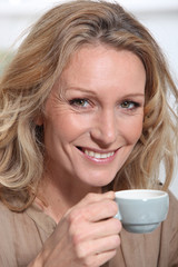 mature blonde woman  with a cup of coffee