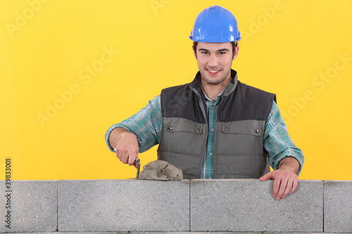 Mason spreading cement on wall with trowel