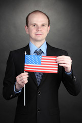 Businessman holding American flag on black background