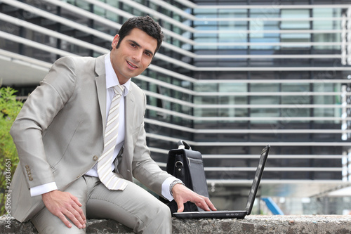 Relaxed director using laptop outdoors