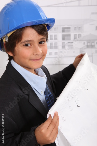 Boy with helmet and blueprints