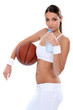 an athletic young woman drinking water and taking a basket ball
