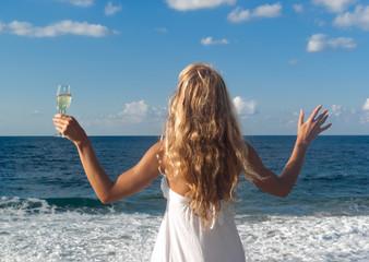 Woman in white dress near sea looking far