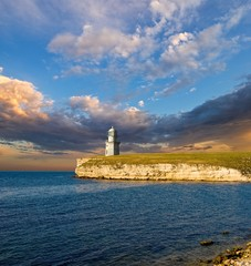 lighthouse on a marine cape by an evening