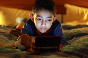 kid in bed wih videogame console
