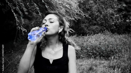 Black & White Woman drinking water from blue bottle