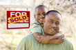 Father and Son In Front of Sold Real Estate Sign