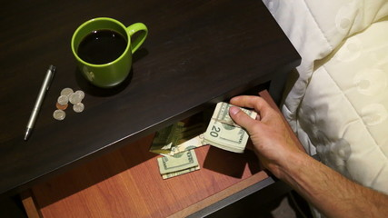 Taking a wad of cash out of the bedside table money drawer.
