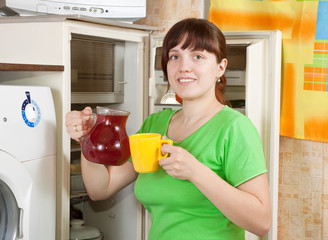 woman  pouring  fruit-drink from refrigerator