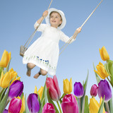 Happy childhood - swinging girl in spring garden poster
