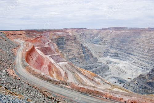 Big mine pit with little dump trucks and reddish soil