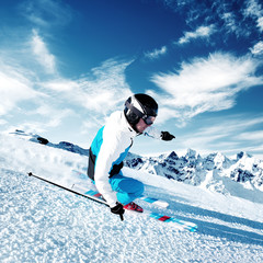 Skier in mountains, prepared piste