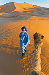 Berber walking with camel at Erg Chebbi, Morocco