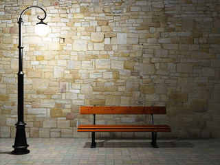 Illuminated brick wall with old street light and bench