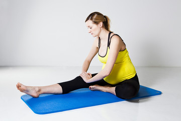 Pregnant woman performing leg stretch