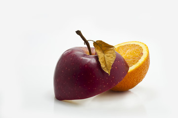 Apple cut on half with orange on white background with leaf