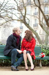 Dating couple sitting on a bench in Paris near the Notre Dame de