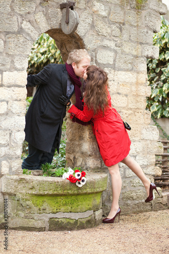 Dating couple kissing near the beautiful wall