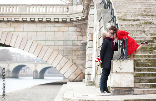 Beautiful romantic couple kissing on a Parisian embankment at sp