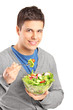 A young man eating salad