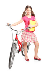 Full length portrait a girl holding a notebooks and a bike