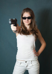 girl in sunglasses aiming a gun