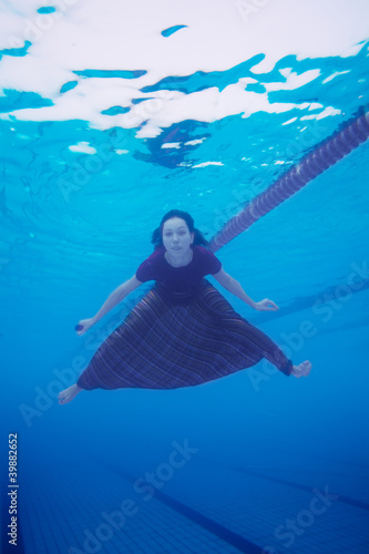 Woman swimming in the pool in  clothes