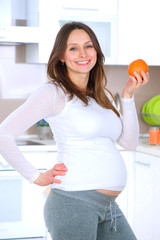 Pregnant Young Woman Eating Fruits at home kitchen