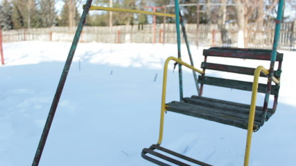 Swing in snowy garden