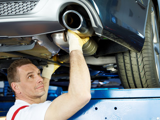 Motor mechanic fixing the exhaust system of a car