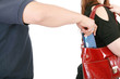 man pickpocketing a purse from woman's bag
