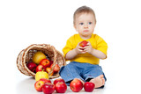 Little boy with healthy food. Near basket with apples.
