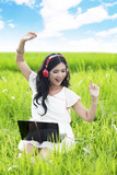 Pretty woman listens to music outdoor