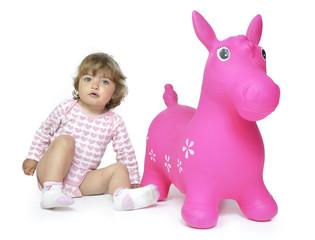 Sentada junto al caballo rosa.