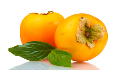 Two appetizing persimmons with green leaves isolated on white