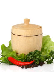 wooden keg on fresh herbs with spices on white