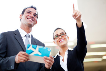 businessman and businesswoman looking at boarding information