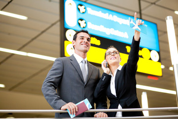 business travellers checking boarding information at airport