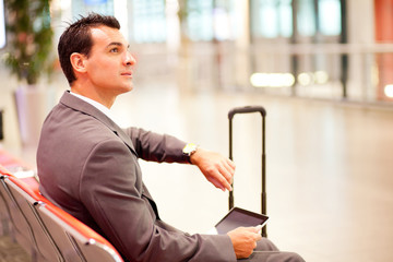 businessman checking time and using tablet at airport