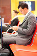 businessman sending or reading text messages at airport