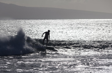 surfer silhoutted against the silver waves on maui coast